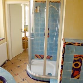 Ein Bad mit handgemachten blauen Fliesen und Bordüren von Guido Kratz