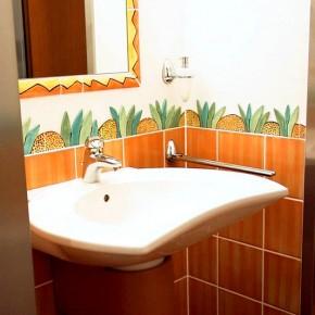 Bad mit handgemachten gelbbraunen Fliesen und Bordueren von Guido Kratz