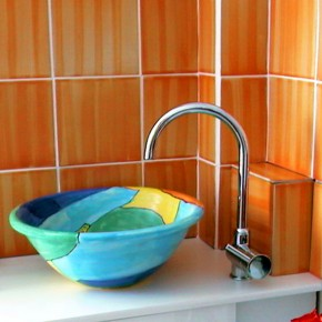 Bemaltes Waschbecken vor terrakottafarbenen Fliesen von Guido Kratz
