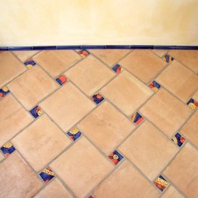 Bodenbelag mit Terrakottafliesen und bemalten Einlegerfliesen